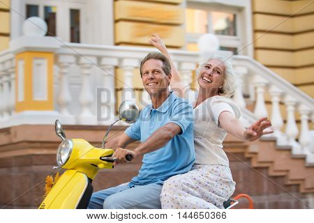 Man and woman riding scooter. Adult couple smiling happily. Good season for vacation. Try and catch us.