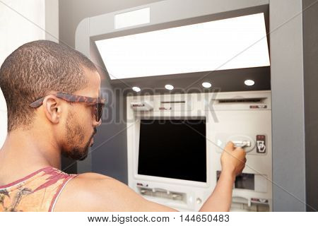 Back Outdoor Shot Of Young Dark-skinned Male Standing Outside In Front Of Atm, Inserting His Plastic
