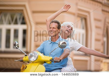 Couple is riding yellow scooter. Smiling guy and lady. Perfect time for a vacation. Feel lighter than air.