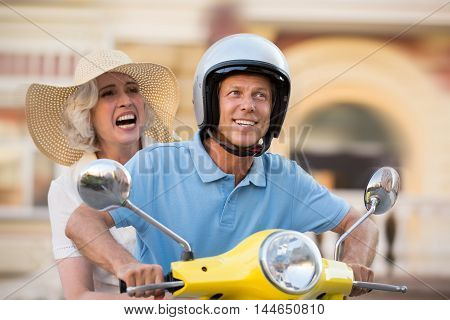 Man and woman on scooter. Guy in helmet is smiling. Adventures wait around every corner. Let's ride across the country.