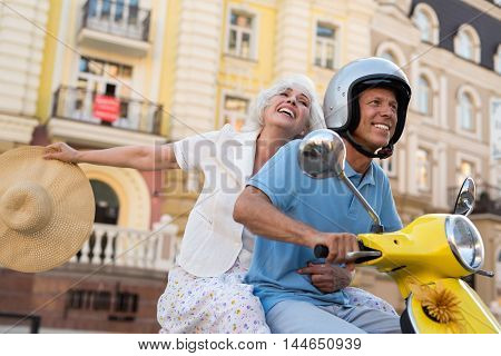Smiling mature couple rides scooter. Man in helmet and woman. Gladness fills the hearts. Adventures are waiting for us.