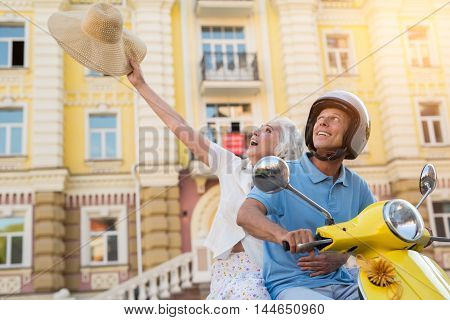 Man on scooter is smiling. Hat in woman's hand. Our dream came true. Happiness without bounds.