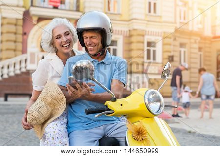 Man on scooter with phone. Mature people are smiling. Connection with those you love. Every day brings joy.