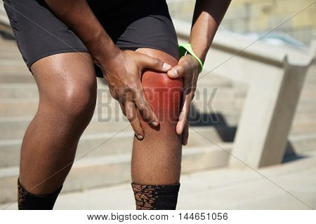 Cropped Shot Of Legs Of African Sportsman With Knee Injury Standing Outdoors, Clasping His Knee Depi