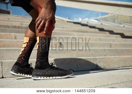 African Jogger Wearing Black Running Shoes Having Strain Or Rupture In His Calf, Massaging It To Soo