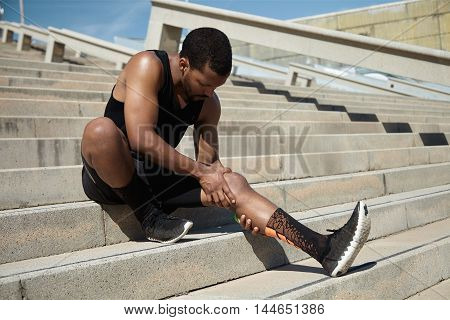 Handsome Black Runner With Muscular Athletic Body Holding His Leg With Both Hands, Feeling Pain In K