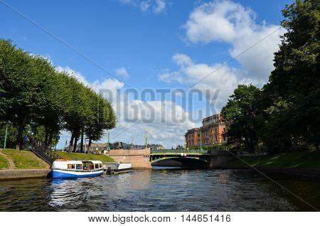 Saint Petersburg, Russia - August 15,2012 - Landscape with the river Fontanka, bridge, walking people and Saint Michael's Castle (Mikhailovsky palace).