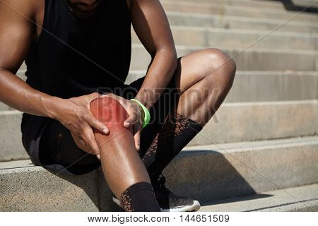 Close Up Shot Of African Athlete In Black Training Socks And Shoes Clutching His Injured Knee, Havin