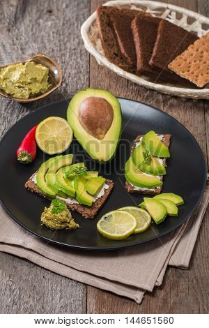 Avocado sandwich with ingredients in plate on wooden background