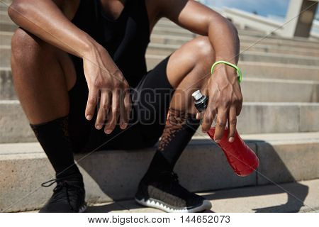 Cropped Portrait Of Tired African Jogger In Black Outfit Holding Bottle With Red Drink Or Shake, Hav