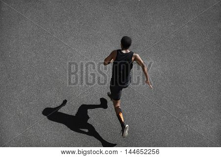 Top View Of Running Man Sprinting For Success On Run. African Muscular Runner Or Jogger Dressed In B