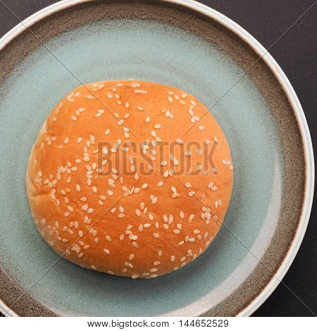 Hamburger bun on a rustic plate top view