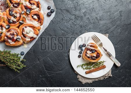 Cinnamon buns with lemon, blueberry and thyme on black background, top view
