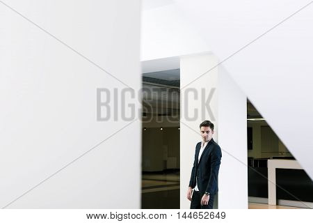 Untypical capture of a young man wearing smart casual clothes in a modern public building
