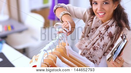 Beautiful young stylist near rack with hangers, isolated