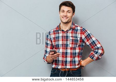 Cheerful young man in headphones listening to music from mobile phone over grey background