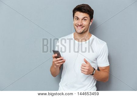 Happy attractive young man listening to music from smartphone and showing thumbs up gesture over gray background