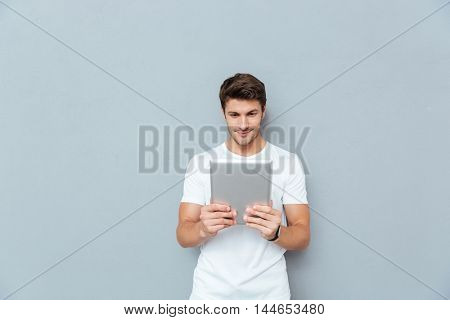 Happy casual man using tablet computer isolated on a gray background