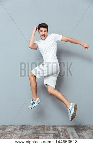Funny crazy man jumping over gray background
