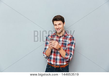 Happy young man in earphones listening to music from smartphone over grey background