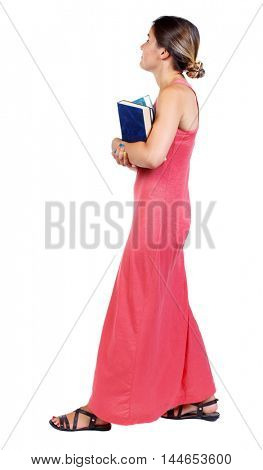 Girl comes with stack of books. side view. slender woman in a long red dress is carrying books and looking up.