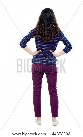 back view of standing young beautiful woman. Long-haired curly girl in blue jacket standing with hands on waist.