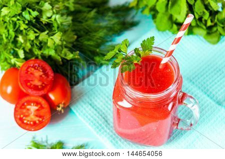 Healthy vegetable. Glass of red tomato juice on wooden table.