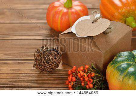 Kraft box and decorative pumpkin on a brown background