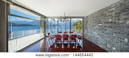 Old dining room of an apartment, red floor and stone wall