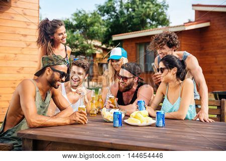 Portrait of cheerful young friends drinking beer outdoor summer party