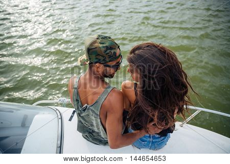 Top view of happy young people sitting and hugging on boat
