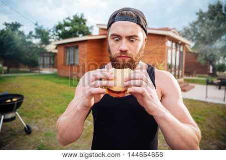 Young bearded hipster guy looking at delicious burger outdoors
