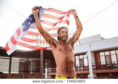 Cheerful attractive african american young man holding flag of United States