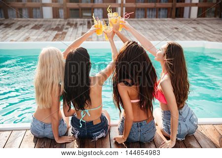 Four laughing cheerful young girls having fun and drinking cocktails at the swimming pool outdoors