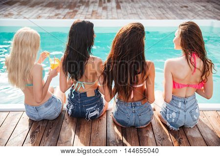 Back view of group of happy young women talking and drinking cocktails near swimming pool
