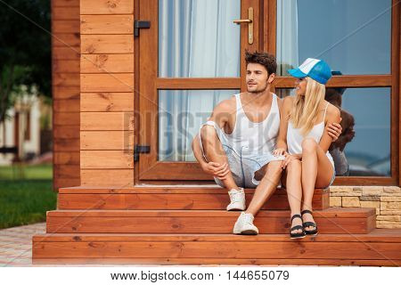 Happy beautiful young couple sitting on porch of wooden house in summer