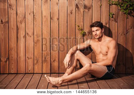 Handsome young man sitting at the poolside and looking at camera over wooden background