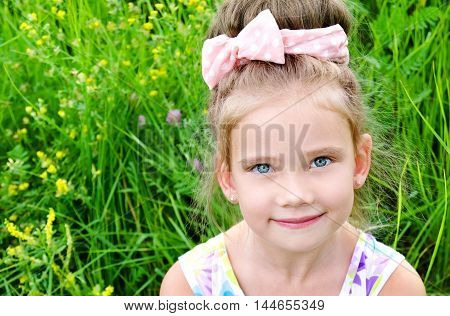 Adorable smiling little girl on the meadow in summer day outdoor