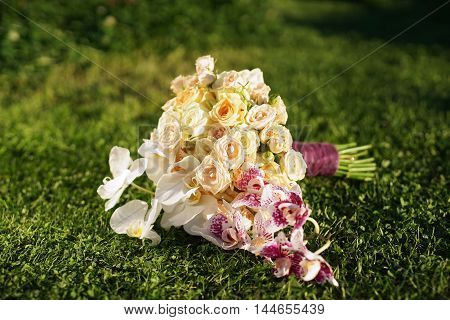 Wedding bouquet of roses and orchids lying on the lawn in the setting sun.