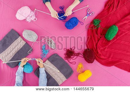 Knitting needle colorful crewel and scissors lying on a pink desktop