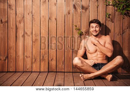 Handsome young excited man sitting and pointing finger away over wooden background