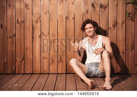 Handsome young smiling man sitting and pointing finger away over wooden background