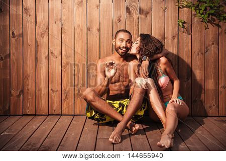 Lovely cheerful mixed race couple showing showing okay sign and kissing over wooden background