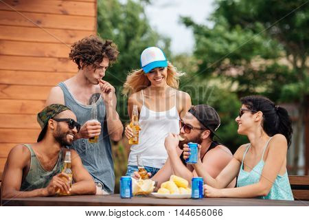 Group of happy young people eating and drinking outdoors