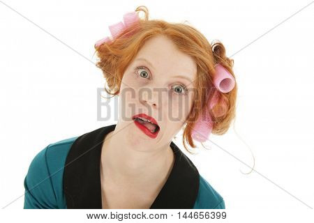 Funny young woman with curlers and lipstick isolated in studio