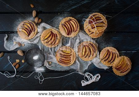 Peach and almond tartlets with powder sugar