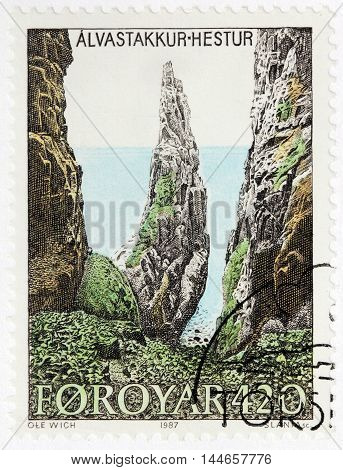 LUGA RUSSIA - JUNE 25 2016: A stamp printed by FAROE ISLANDS shows view of Alvastakkur - a point in Faroe Islands and is nearby to Nakkur Eggjastakkur and Hestur circa 1987.