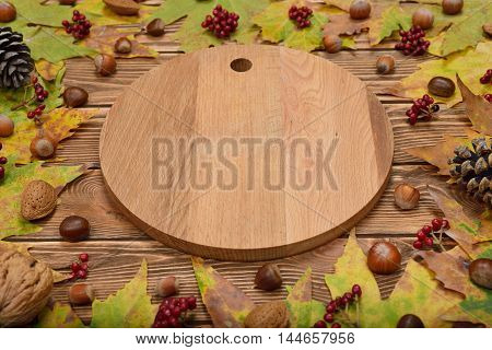 Autumn leaves and round board on a brown background