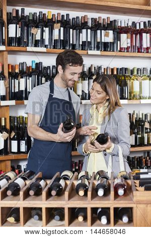 Salesman Discussing Over Wine Bottles With Customer