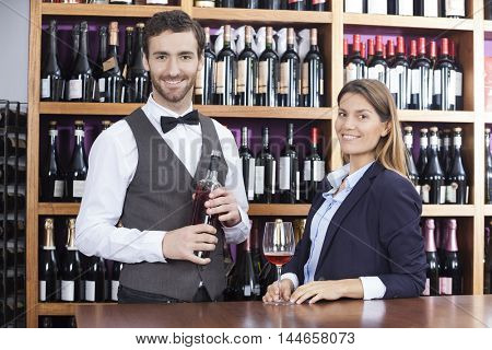 Portrait Of Customer And Bartender With Red Wine At Counter